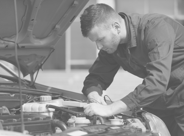 A mechanic works on a diesel engine.
