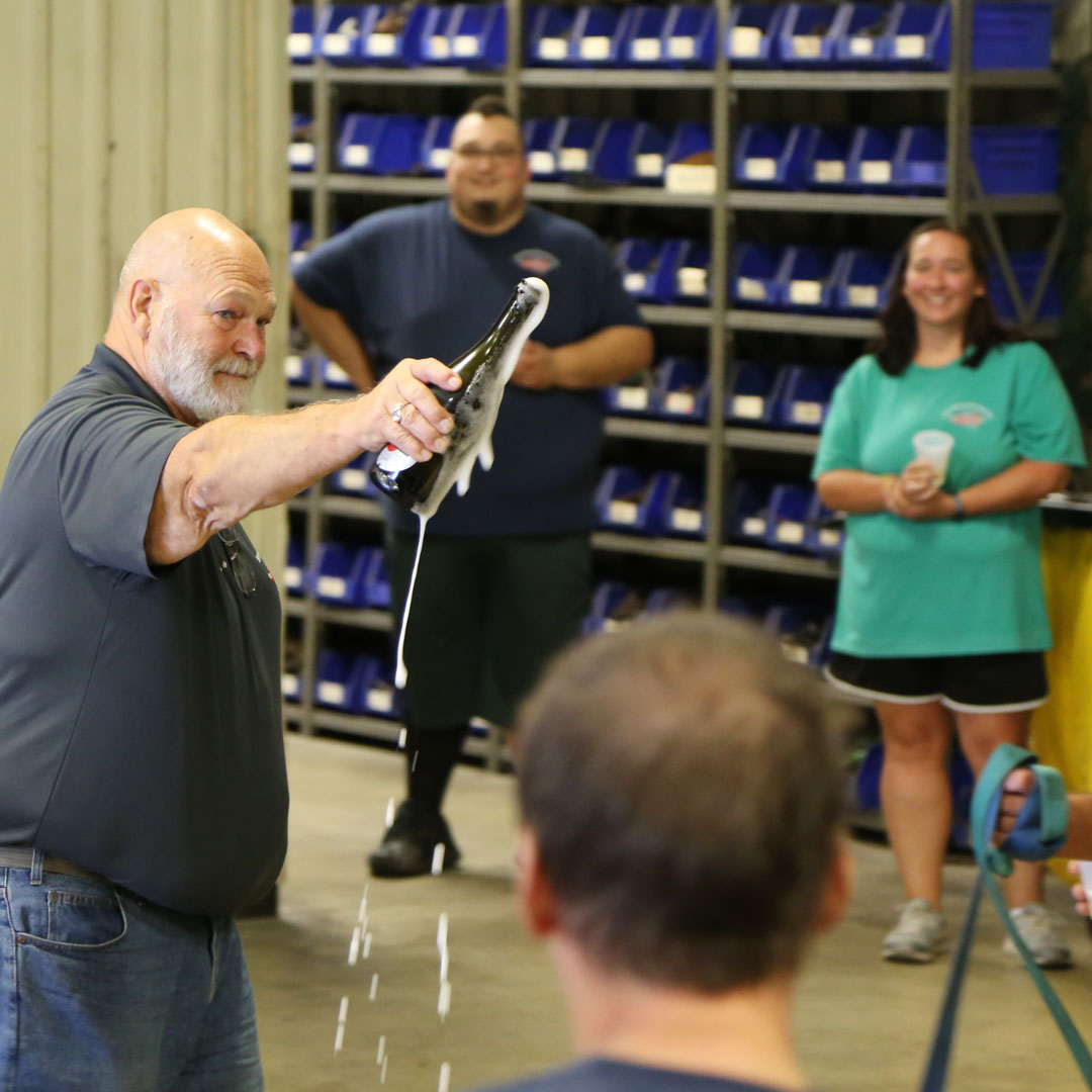 President, Val Leefers, pops the champagne to toast Area Diesel Service's sucess.